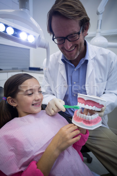 Dentist showing young patient how to brush teeth Stock photo © wavebreak_media