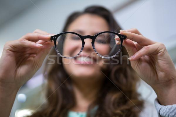 Female customer holding spectacles in optical store Stock photo © wavebreak_media