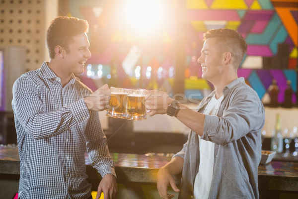 Two male friends toasting beer mugs at bar counter Stock photo © wavebreak_media