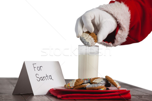 Close-up of santa claus dipping cookies in a glass of milk Stock photo © wavebreak_media