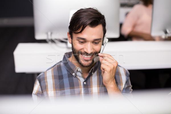 Smiling male customer service executive talking on headset at desk Stock photo © wavebreak_media