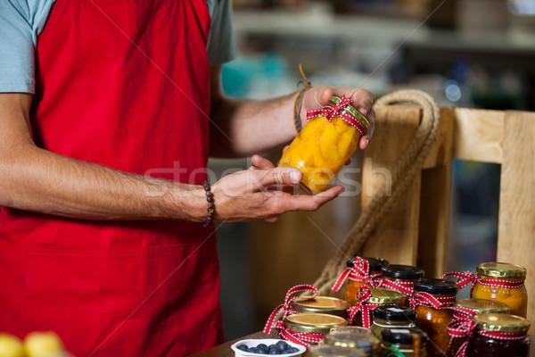 Staff checking pickle jar at counter in market Stock photo © wavebreak_media