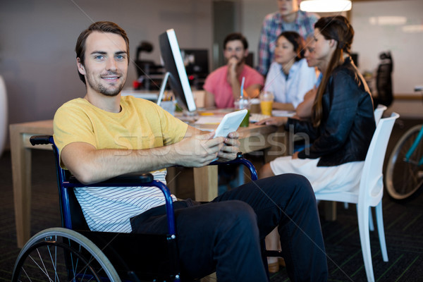 Physically disabled man on wheelchair using tablet in office Stock photo © wavebreak_media