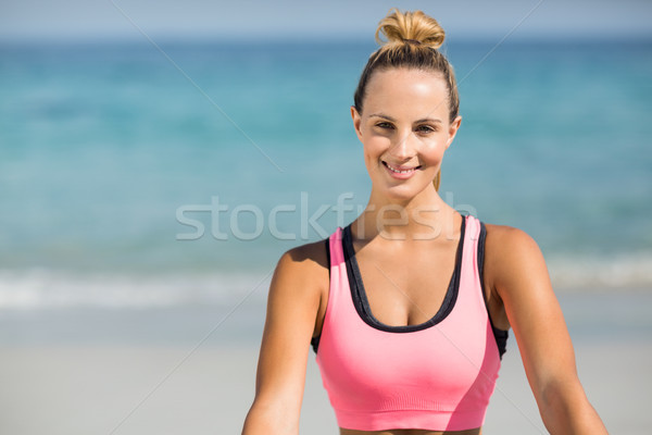 Beautiful woman smiling while sitting at beach Stock photo © wavebreak_media