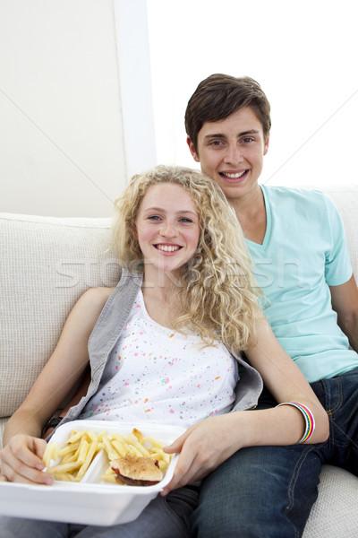 Teen couple eating burgers and fries Stock photo © wavebreak_media