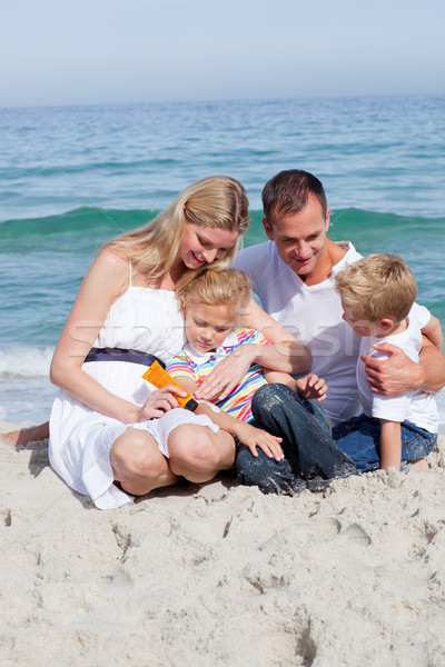 Smiling mother with her family holding sunscreen Stock photo © wavebreak_media