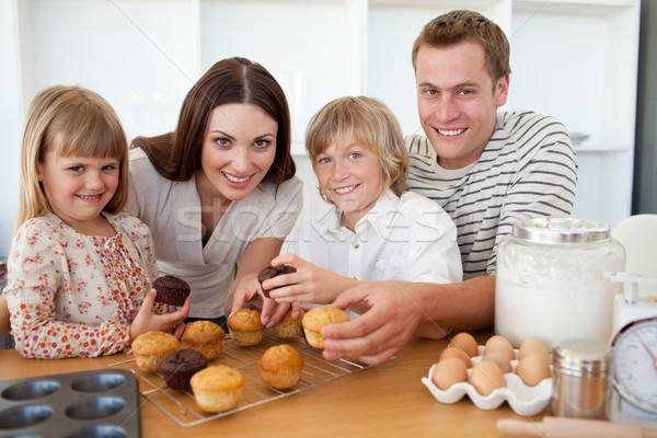 Smiling family eating their muffins in the kitchen Stock photo © wavebreak_media