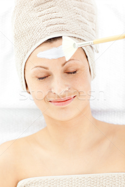 Resting young woman receiving white cream on her face in a spa center Stock photo © wavebreak_media