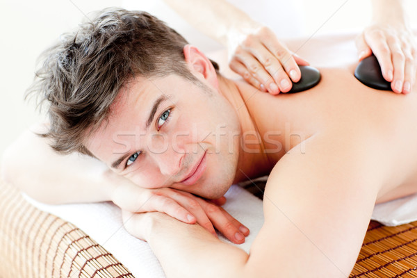 Stock photo: Handsome man receiving a back massage with hot stone in a spa center