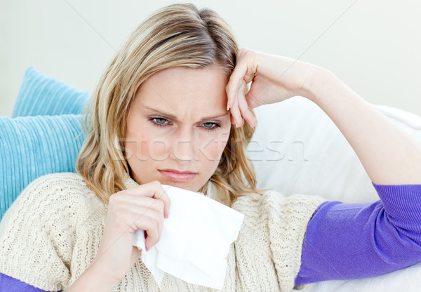 Diseased woman lying on a sofa with tissues against a white background Stock photo © wavebreak_media