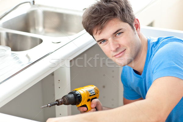 Handsome man holding a drill repairing a kitchen sink at home Stock photo © wavebreak_media