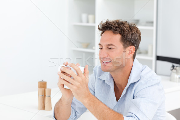 Attractive man drinking coffee sitting at a table in the kitchen Stock photo © wavebreak_media