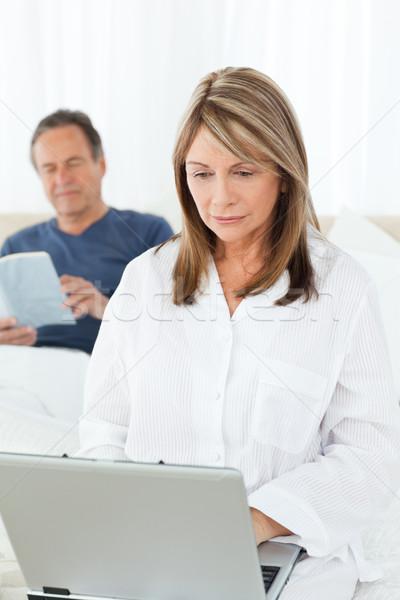 Frau schauen Laptop Ehemann Lesung Bett Stock foto © wavebreak_media
