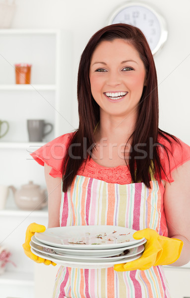 Beautiful red-haired woman holding some dirty plates in the kitchen in her appartment Stock photo © wavebreak_media