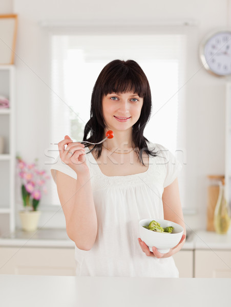 Cute brunette female eating a cherry tomato while holding a bowl of vegetables in the kitchen Stock photo © wavebreak_media