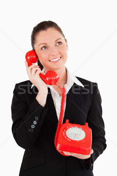 Gorgeous woman in suit on the phone while standing against a white background Stock photo © wavebreak_media