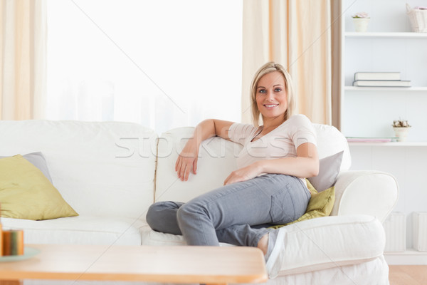 Relaxed woman sitting on a sofa in her living room Stock photo © wavebreak_media