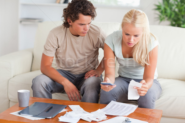 Shocked couple calculating their expenses in the living room Stock photo © wavebreak_media