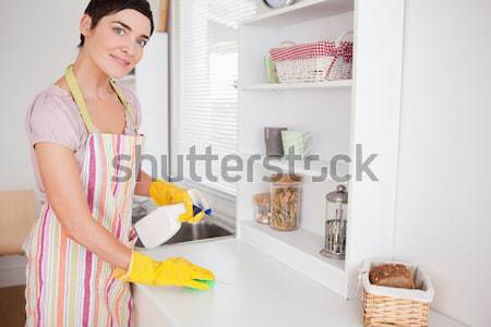 Stock photo: Beautiful brunette woman cleaning a cupboard in the kitchen