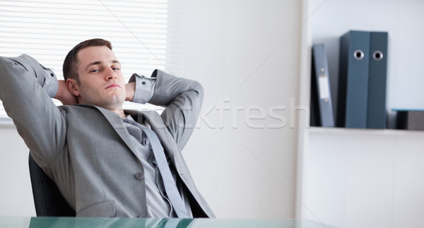 Young businessman relaxing sitting behind a table Stock photo © wavebreak_media