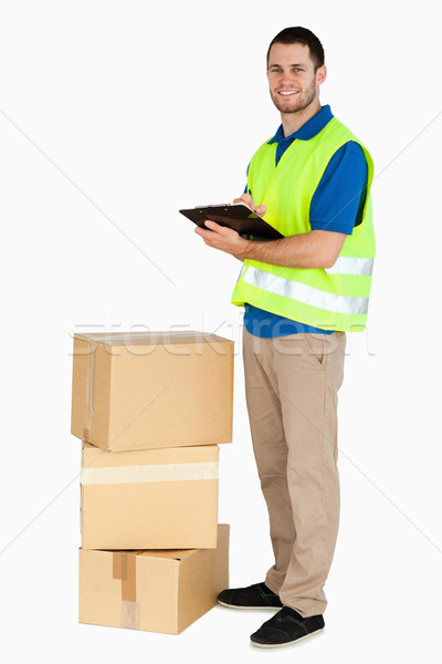 Side view of smiling young delivery man against a white background Stock photo © wavebreak_media
