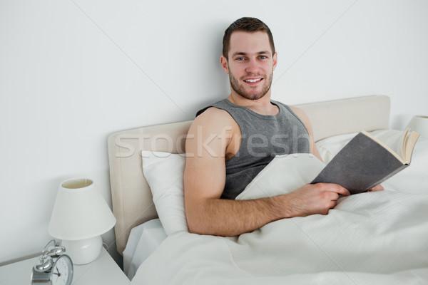 Smiling man reading a novel in his bedroom Stock photo © wavebreak_media