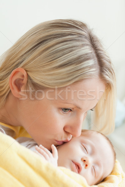 Affectionate young mother kissing her sleeping baby's cheek Stock photo © wavebreak_media