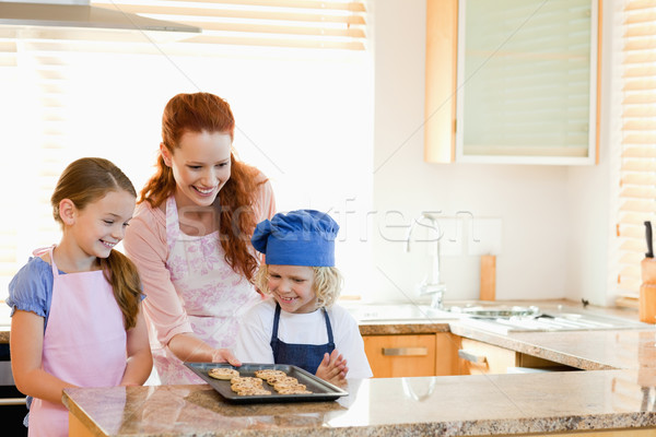 Smiling mother presenting finished cookies to her children Stock photo © wavebreak_media