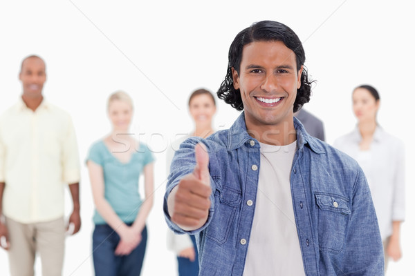 Close-up of a man with his thumb-up with people behind against white background Stock photo © wavebreak_media