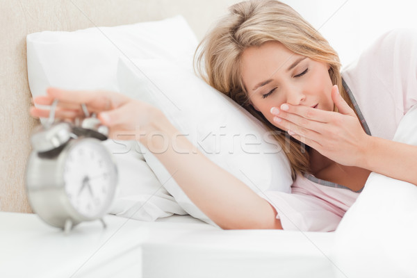 A woman in bed is moving her hand to turn off her alarm, while her eyes are closed Stock photo © wavebreak_media