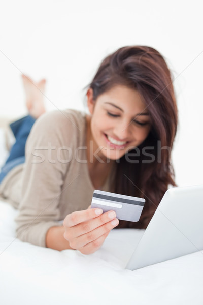 A close up focus shot on the credit card that the smiling woman is holding as she uses her tablet. Stock photo © wavebreak_media