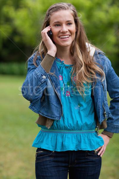 Gülen genç kız konuşma cep telefonu ayakta Stok fotoğraf © wavebreak_media