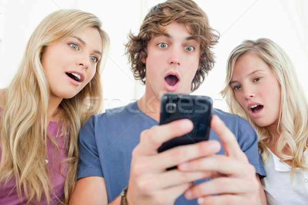 A group of friends look at the phone screen in shock  Stock photo © wavebreak_media