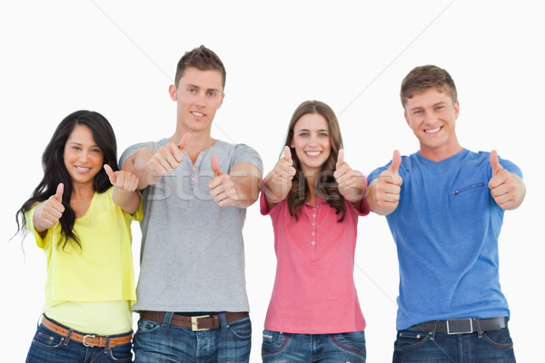 A smiling group of friends give a thumbs up while looking at the camera  Stock photo © wavebreak_media