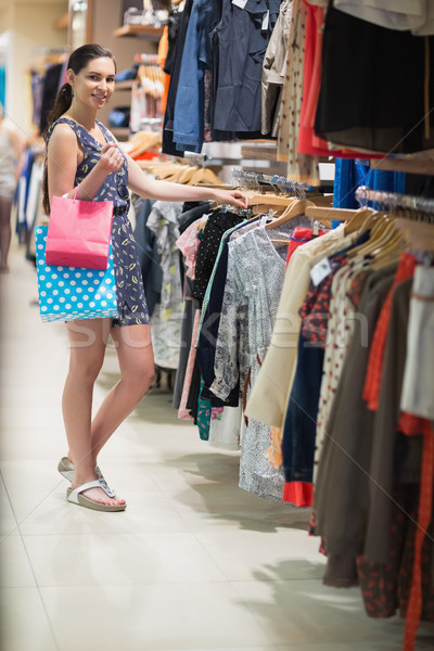 Woman is standing at the clothes rack searching in the shopping mall  Stock photo © wavebreak_media
