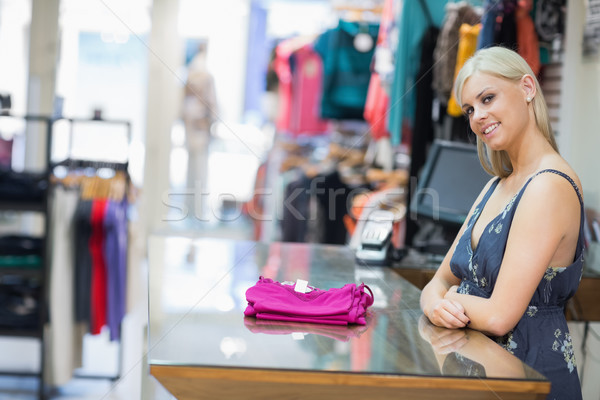 Woman smiling behind counter with folded clothes in clothing store Stock photo © wavebreak_media