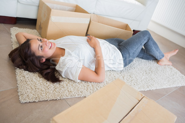 Woman lying on the carpet surrounded by moving boxes in living room Stock photo © wavebreak_media