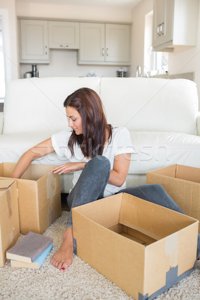 Woman happily unpacking moving boxes in living room Stock photo © wavebreak_media
