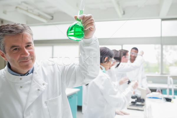 Chemist happily hold ing beaker of green liquid in bus ylab Stock photo © wavebreak_media