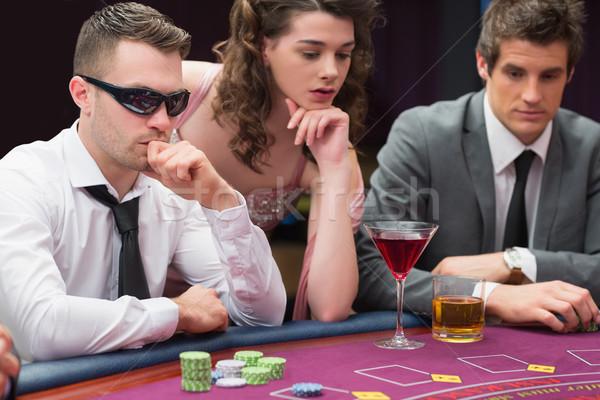 Homens mulher sessão pôquer tabela cassino Foto stock © wavebreak_media
