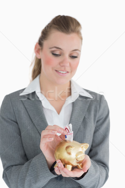 Businesswoman putting money in the piggy-bank while saving Stock photo © wavebreak_media
