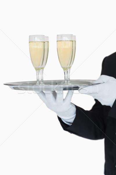 Stock photo: Waiter holding tray of champagne flutes on white background