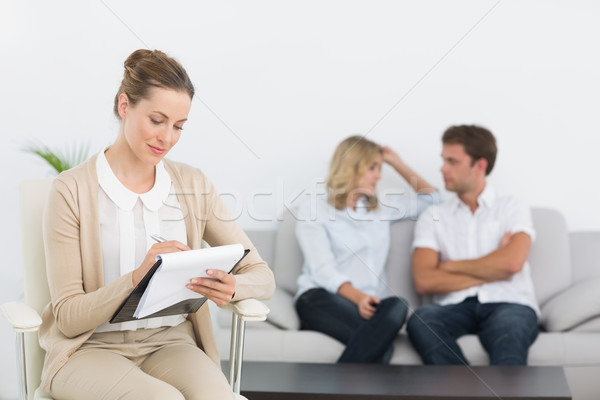 Financial adviser writing notes with couple in background Stock photo © wavebreak_media