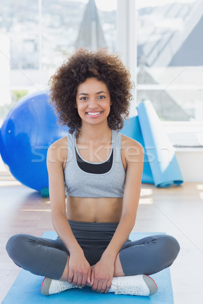 Stock photo: Fit woman sitting on exercise mat in fitness studio