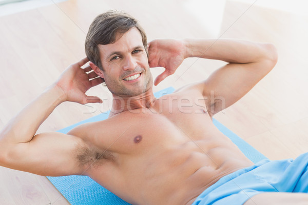 Smiling shirtless young man doing sit ups in fitness studio Stock photo © wavebreak_media