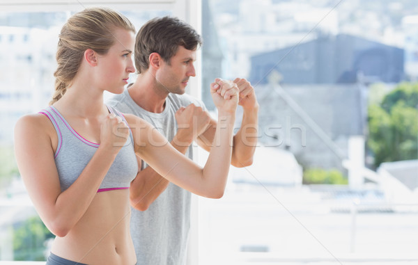 Serious couple standing in boxing stance in fitness studio Stock photo © wavebreak_media