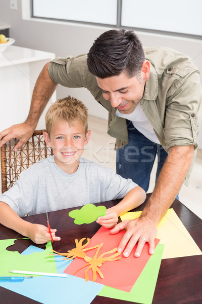 Father and smiling son making paper shapes together at the table Stock photo © wavebreak_media
