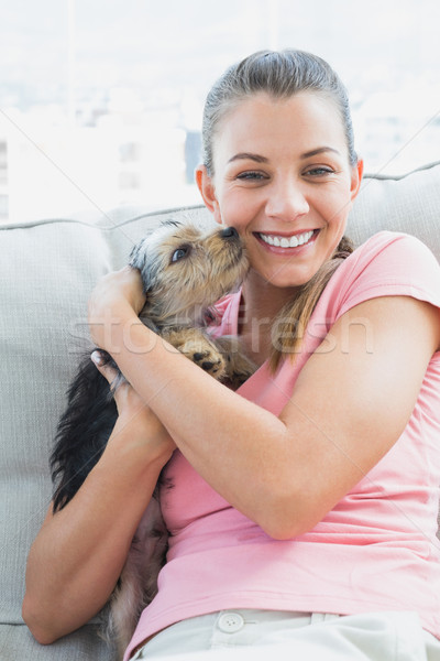 Pretty woman cuddling her yorkshire terrier on the couch Stock photo © wavebreak_media