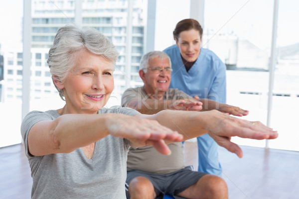 Female therapist assisting senior couple with exercises Stock photo © wavebreak_media