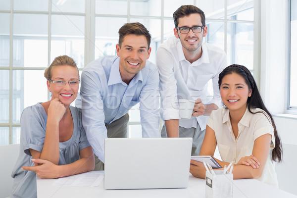 Casual business team smiling at camera together at desk Stock photo © wavebreak_media